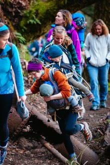 Kim Ives, with her two children attached, steps over an old pipe during a Hike It Baby excursion at the Upper McCord Creek trail in the Columbia River Gorge.